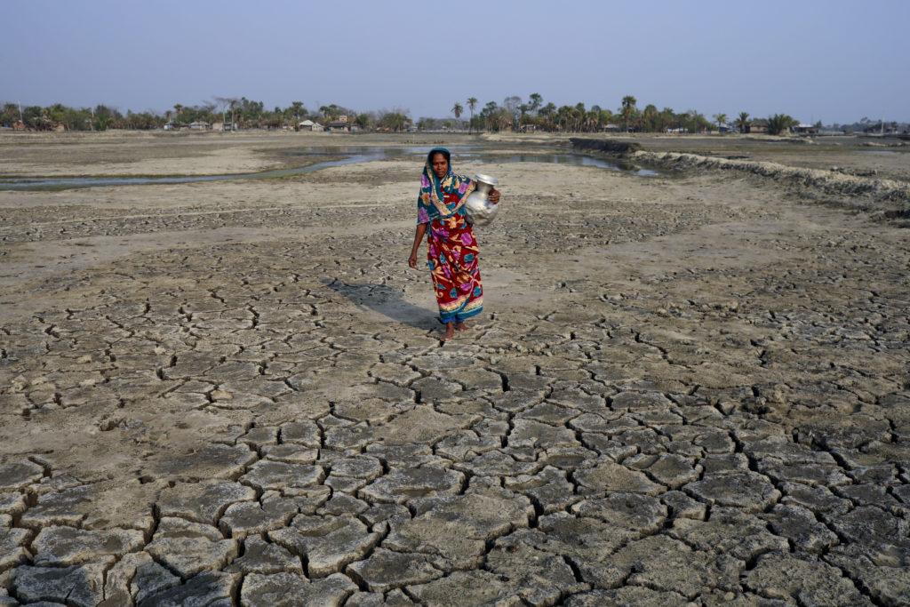 Ein Frau holt Trinkwasser in einem Krug. Sie läuft über ein ausgetrocknetes Feld.